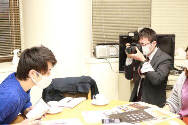 北日本新聞の記者さんから取材を受けているふくの~とメンバー